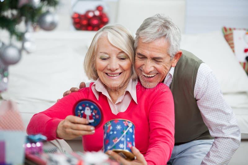 Szczęśliwa Starsza para Patrzeje Bożenarodzeniowego prezent obrazy royalty free