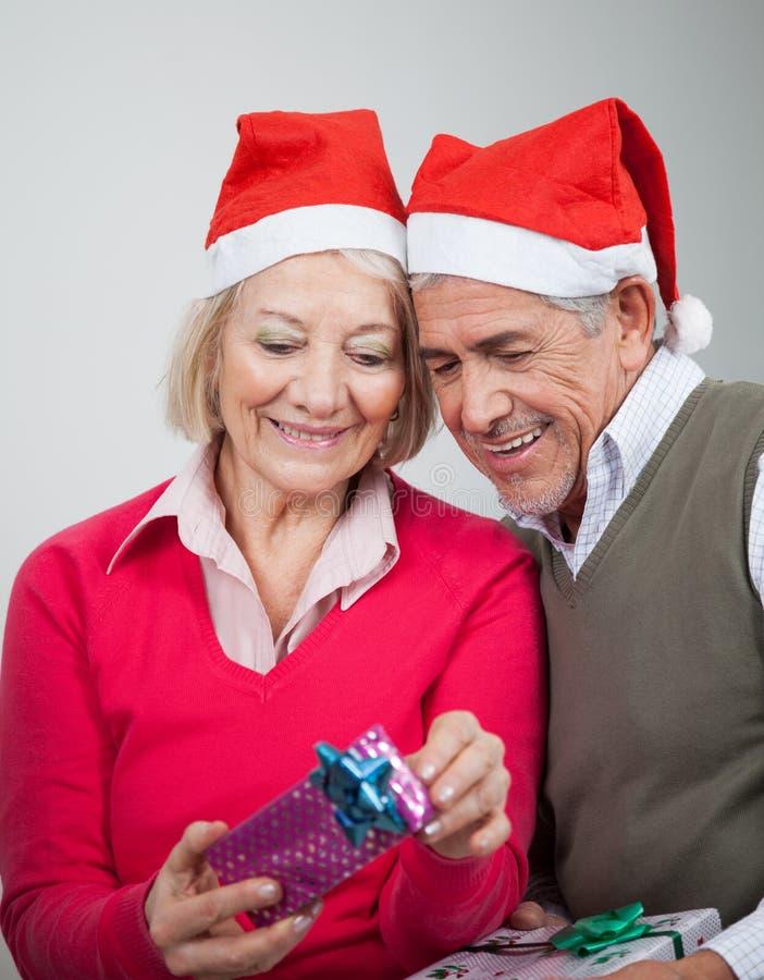 Szczęśliwa Starsza para Patrzeje Bożenarodzeniowych prezenty zdjęcie royalty free