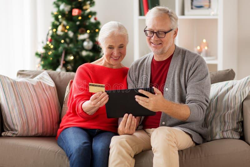 Szczęśliwa starsza para z pastylka komputerem osobistym przy bożymi narodzeniami obraz royalty free