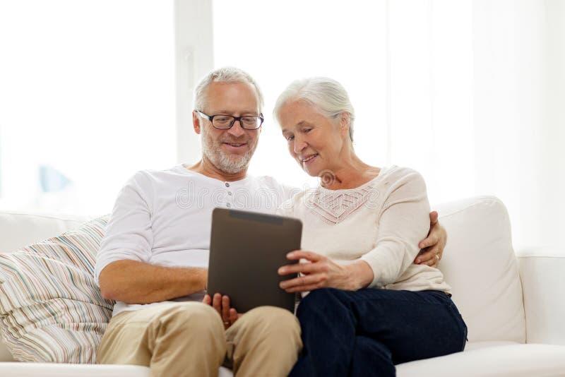 Szczęśliwa starsza para z pastylka komputerem osobistym w domu zdjęcia royalty free