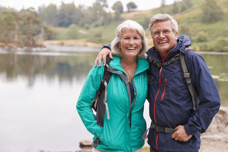 Szczęśliwa starsza pary pozycja na brzeg jezioro ono uśmiecha się kamera, Jeziorny okręg, UK zdjęcia stock