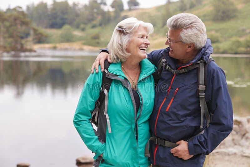 Szczęśliwa starsza pary pozycja na brzeg jezioro ono uśmiecha się przy each inny, Jeziorny okręg, UK obrazy royalty free