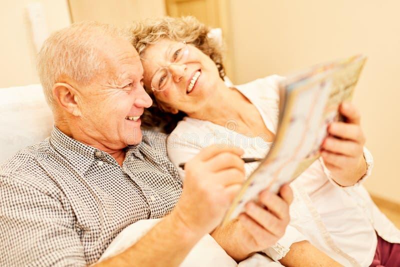 Szczęśliwa starszej osoby para rozwiązuje łamigłówki fotografia stock