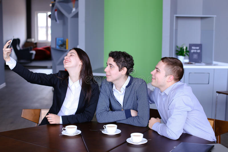 Szczęśliwa studencka dziewczyna, dwa mężczyzna robi selfie na smartphone i ponowny obraz royalty free