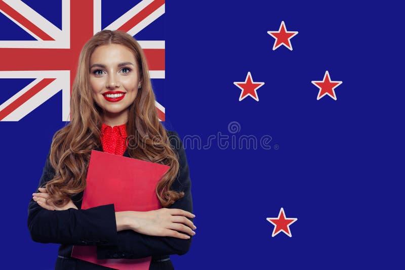 Szczęśliwa studencka dziewczyna z książką przeciw Nowa Zelandia fladze obraz royalty free