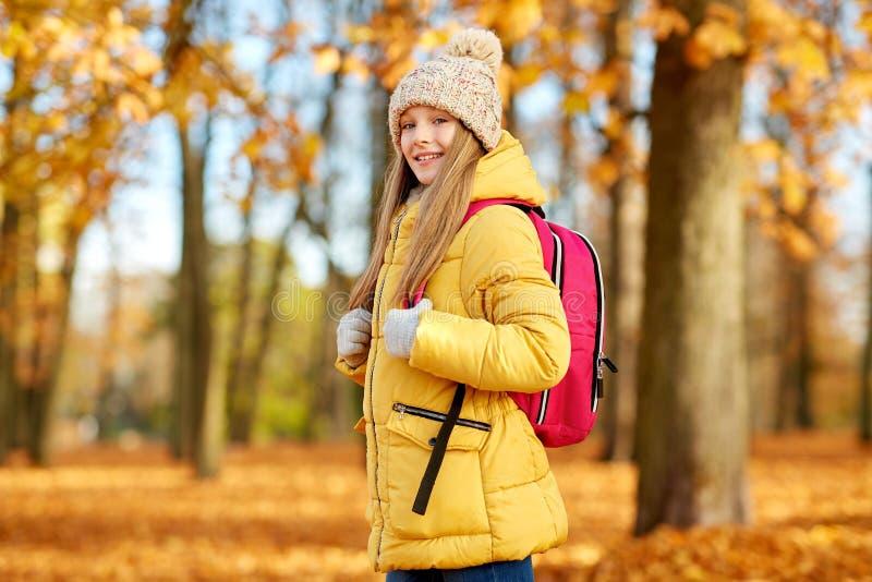 Szczęśliwa studencka dziewczyna z schoolbag przy jesień parkiem zdjęcie royalty free