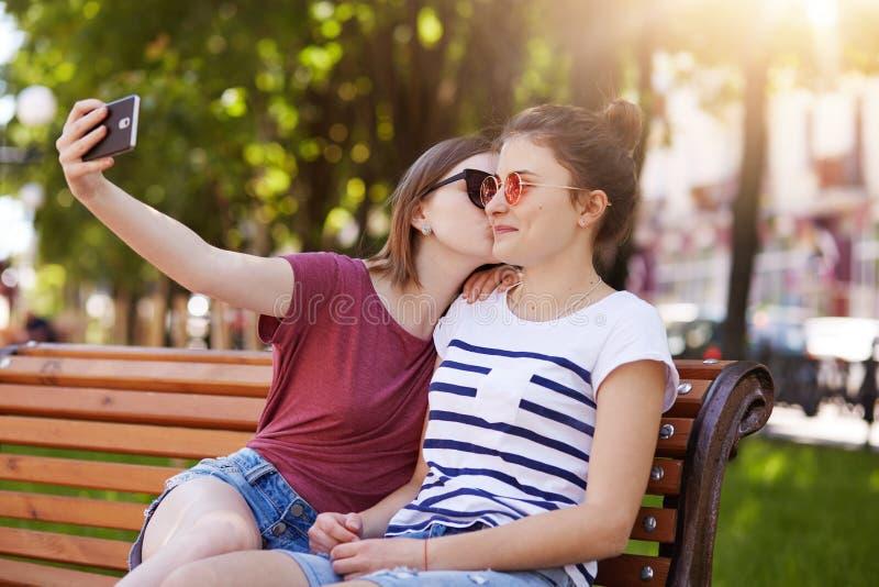 Szczęśliwa szczera dwa dziewczyny robią selfie na drewnianej ławki obsiadaniu w parku Rozochocona młoda dziewczyna całuje jej naj obrazy stock
