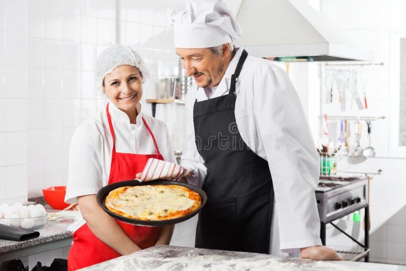 Szczęśliwa szef kuchni pozycja kolegi mienia pizzy niecką zdjęcia royalty free