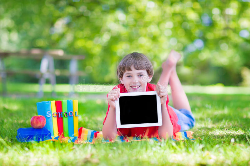 Szczęśliwa szkolna chłopiec z pastylka komputerem osobistym zdjęcie royalty free