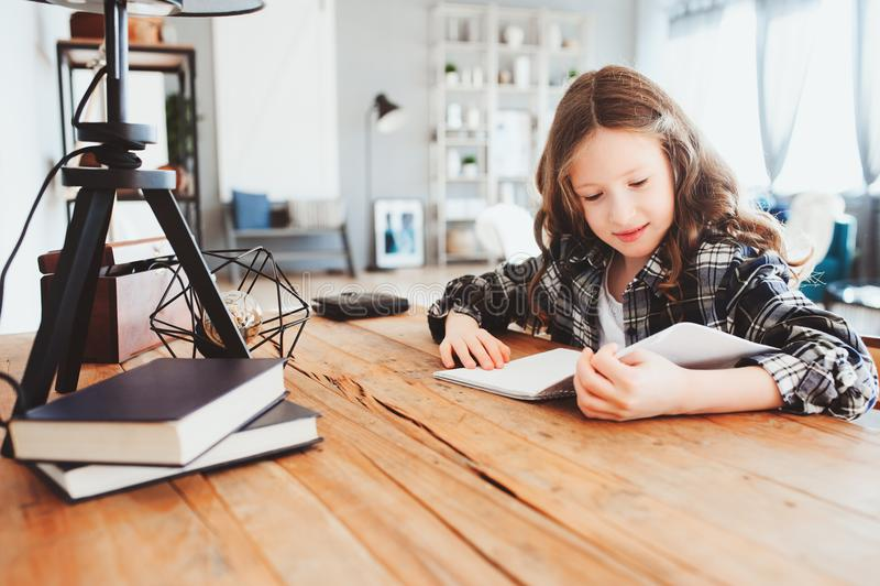 Szczęśliwa szkolna dziewczyna robi pracie domowej Mądrze dziecko pracuje mocno i pisze obrazy stock