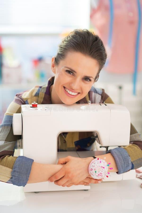 Szczęśliwa szwaczka obejmuje szwalną maszynę zdjęcie stock