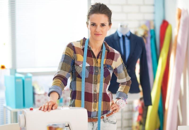 Szczęśliwa szwaczka w pracownianym pobliskim sewingmachine obrazy stock