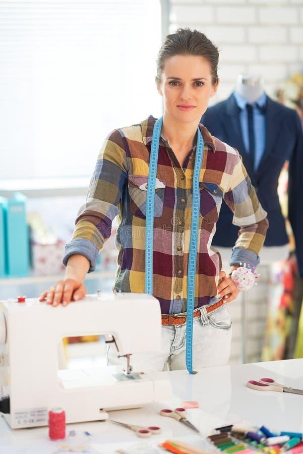Szczęśliwa szwaczka w pracownianym pobliskim sewingmachine obrazy royalty free