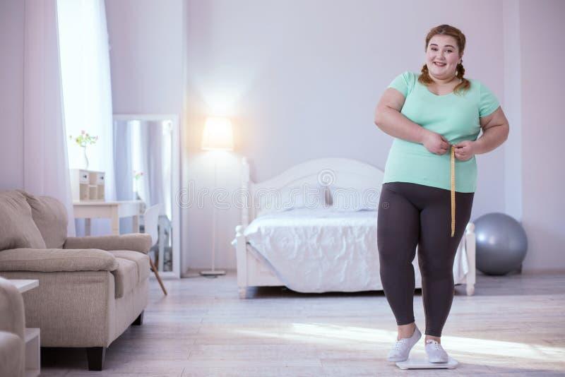 Szczęśliwa tłuściuchna kobieta pokazuje jej osiągnięcie zdjęcie royalty free