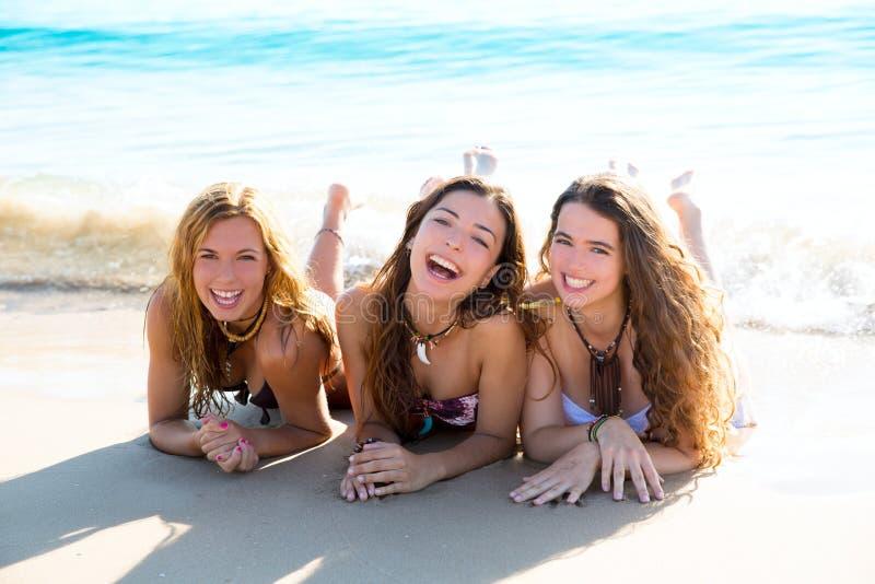 Szczęśliwa trzy przyjaciel dziewczyny kłama na plażowy piaska ono uśmiecha się obrazy royalty free