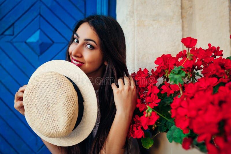 Szczęśliwa turystyczna kobieta ono uśmiecha się przeciw błękitnemu tłu czerwienią kwitnie outdoors twój wakacje rodzinny szczęśli obrazy royalty free