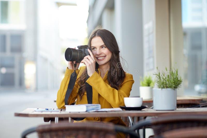 Szczęśliwa turystyczna kobieta z kamerą przy miasto kawiarnią obrazy royalty free