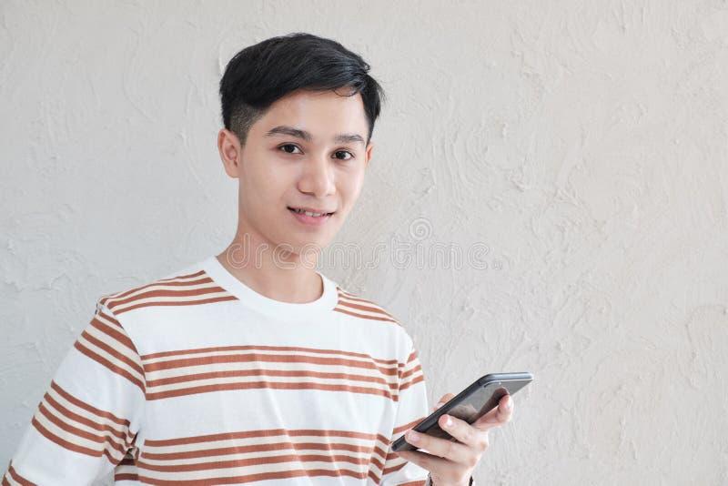 Szczęśliwa twarz, portret zaufanie przystojny młody azjatykci mężczyzna jest ubranym pasiastą koszulkę używać smartphone obraz royalty free