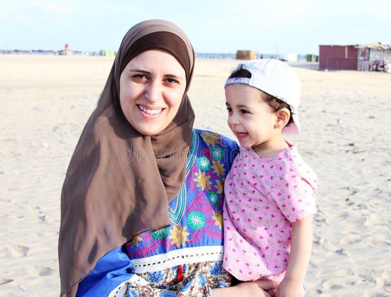 Szczęśliwa uśmiechnięta arabska muzułmańska dziewczynka z jej matką obraz royalty free