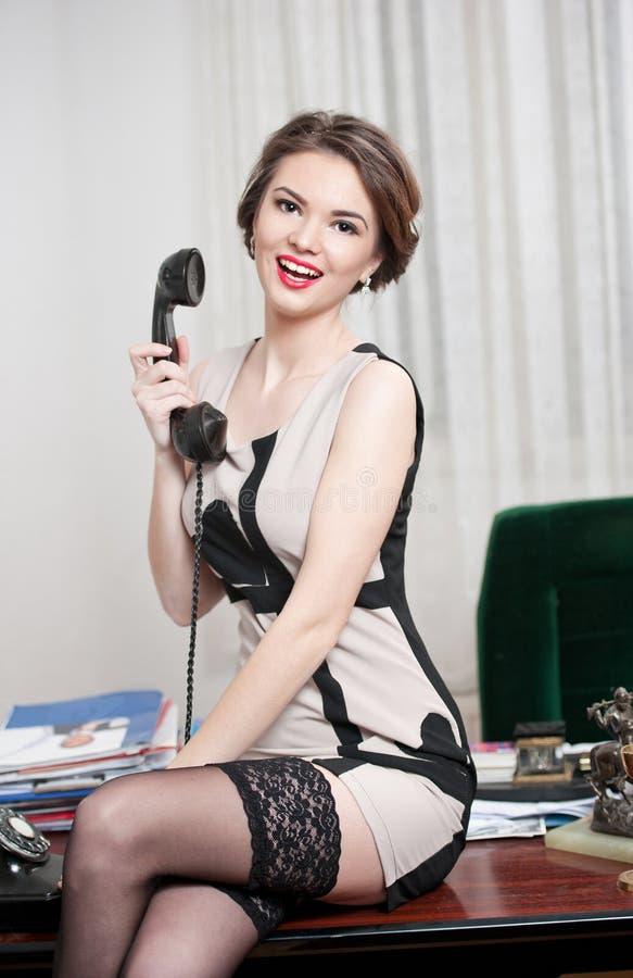 Szczęśliwa uśmiechnięta atrakcyjna kobieta jest ubranym elegancką suknię opowiada telefonem w biurowej scenerii czarne pończochy i fotografia royalty free