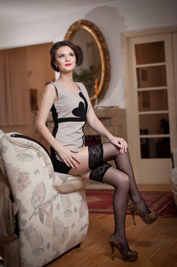 Szczęśliwa uśmiechnięta atrakcyjna kobieta jest ubranym elegancką suknię siedzi na kanapy ręce czarne pończochy i Piękna młoda zm fotografia stock
