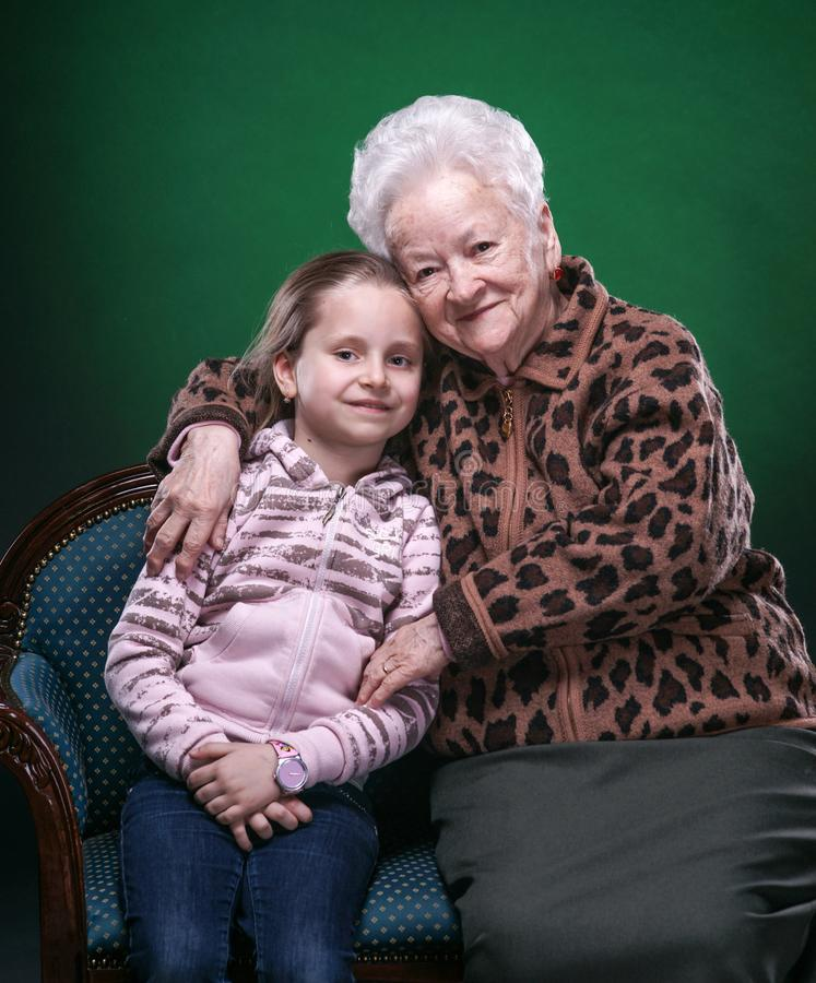 Szczęśliwa uśmiechnięta babcia i wnuczka pozuje w studiu obrazy stock