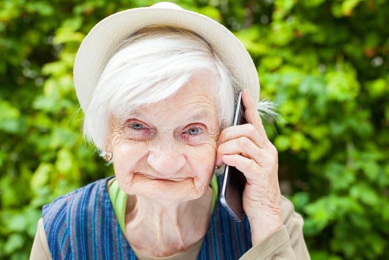 Szczęśliwa uśmiechnięta babcia opowiada na telefonie komórkowym obraz royalty free