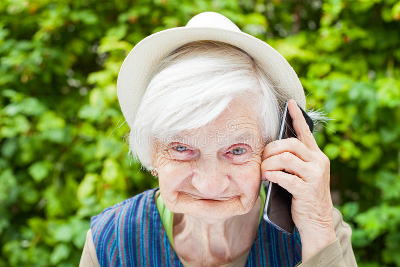 Szczęśliwa uśmiechnięta babcia opowiada na telefonie komórkowym fotografia royalty free