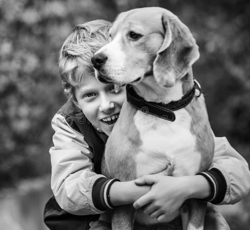 Szczęśliwa uśmiechnięta chłopiec ściska jego najlepszego przyjaciela beagle psa zdjęcie royalty free