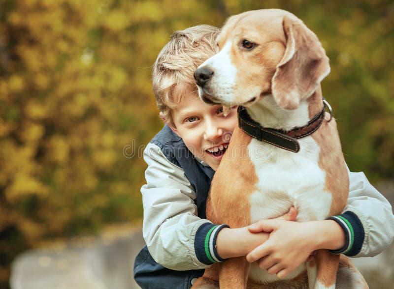 Szczęśliwa uśmiechnięta chłopiec ściska jego najlepszego przyjaciela beagle psa obrazy royalty free
