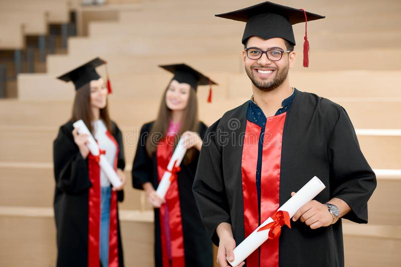 Szczęśliwa uśmiechnięta chłopiec utrzymuje uniwersyteckiego dyplom fotografia royalty free