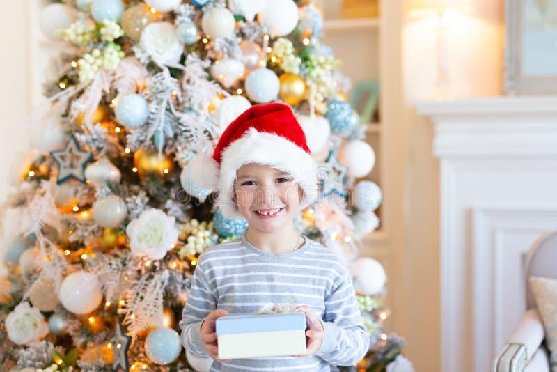 Szczęśliwa uśmiechnięta chłopiec w Santa kapeluszu z prezenta pudełkiem nad choinką zaświeca tło bożych narodzeń pojęcia nowy rok zdjęcie royalty free