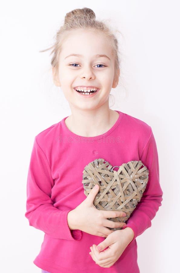 Szczęśliwa uśmiechnięta dziecko dziewczyna z kierowym symbolem - kocha pojęcie zdjęcia stock