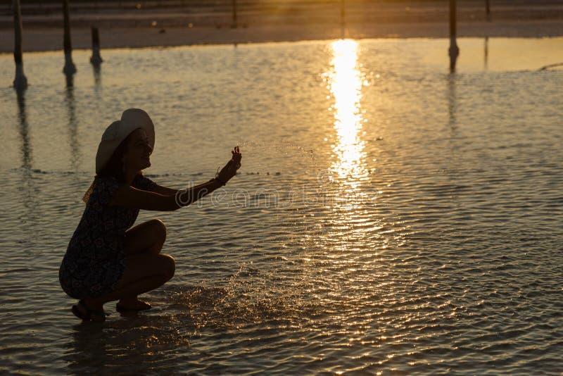 Szczęśliwa uśmiechnięta dziewczyna cieszy się słońce, kropi słoną wodę jezioro w promieniach zmierzch zdjęcie royalty free