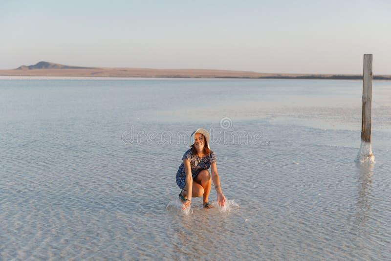 Szczęśliwa uśmiechnięta dziewczyna cieszy się słońce, kropi słoną wodę jezioro w promieniach zmierzch zdjęcia stock