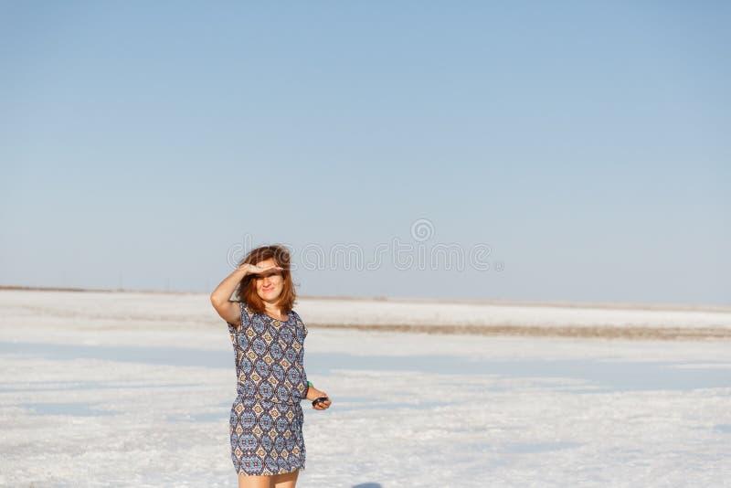 Szczęśliwa uśmiechnięta dziewczyna cieszy się słońce, tana i śmiechy, chwyt ręka przy jego czołem zdjęcia royalty free