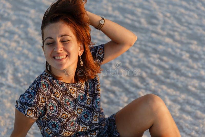 Szczęśliwa uśmiechnięta dziewczyna cieszy się zmierzchu słońce i trząść jej głowę, siedzi na soli obraz royalty free