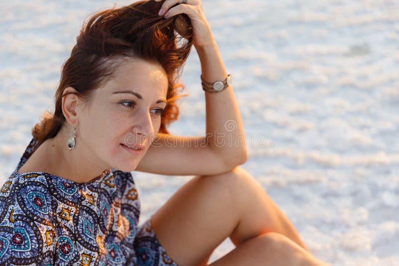 Szczęśliwa uśmiechnięta dziewczyna cieszy się zmierzchu słońce i trząść jej głowę, siedzi na soli fotografia royalty free