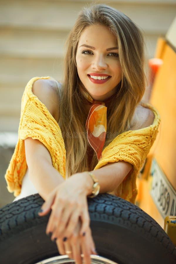 Szczęśliwa uśmiechnięta dziewczyna jest ubranym żółtego pulower pozuje z auto kołem blisko starego retro autobusu, jesieni pojęci fotografia stock