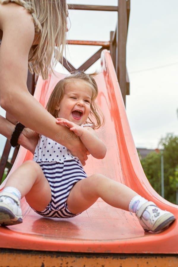 Szczęśliwa uśmiechnięta dziewczyna ono ślizga się w dół na obruszeniu fotografia royalty free