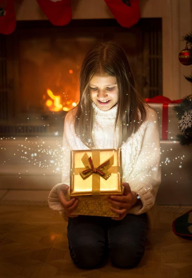 Szczęśliwa uśmiechnięta dziewczyna otwiera błyszczącego Bożenarodzeniowego prezenta pudełko Światło i s zdjęcie stock