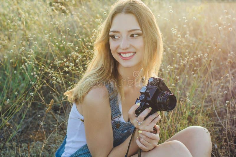 Szczęśliwa uśmiechnięta dziewczyna robi obrazkom starą kamerą obrazy stock