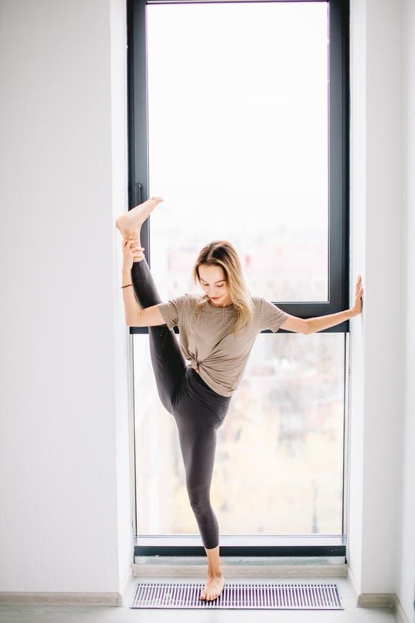 Szczęśliwa uśmiechnięta gimnastyczki dziewczyna jest ubranym opracowywać w nowożytnym studiu obrazy stock