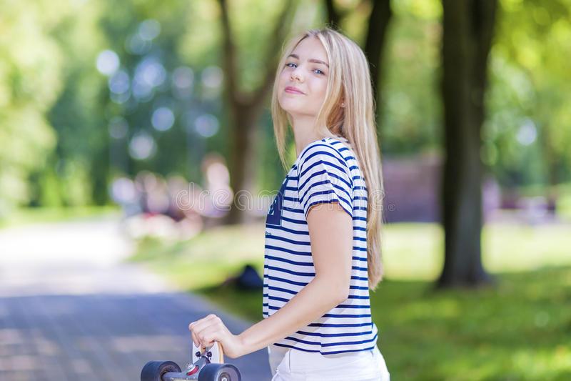 Szczęśliwa Uśmiechnięta Kaukaska nastoletnia dziewczyna Pozuje Z Długi deskorolka Outdoors zdjęcia stock