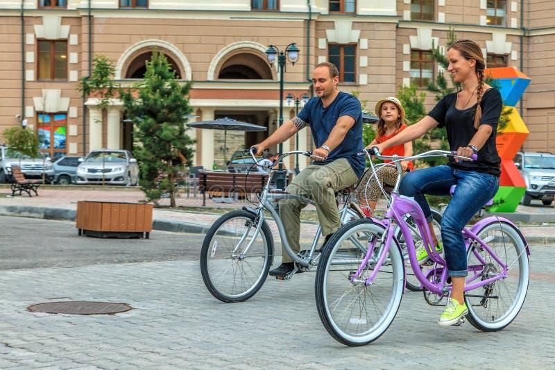 Szczęśliwa uśmiechnięta Kaukaska rodzina ojciec, matka i córka, jedziemy bicykle outdoors w ulicie przy kurortem zdjęcia stock