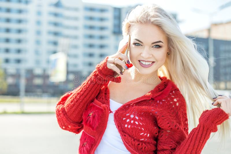 Szczęśliwa uśmiechnięta kobieta jest ubranym czerwonego pulower mówi na telefonie komórkowym obraz stock