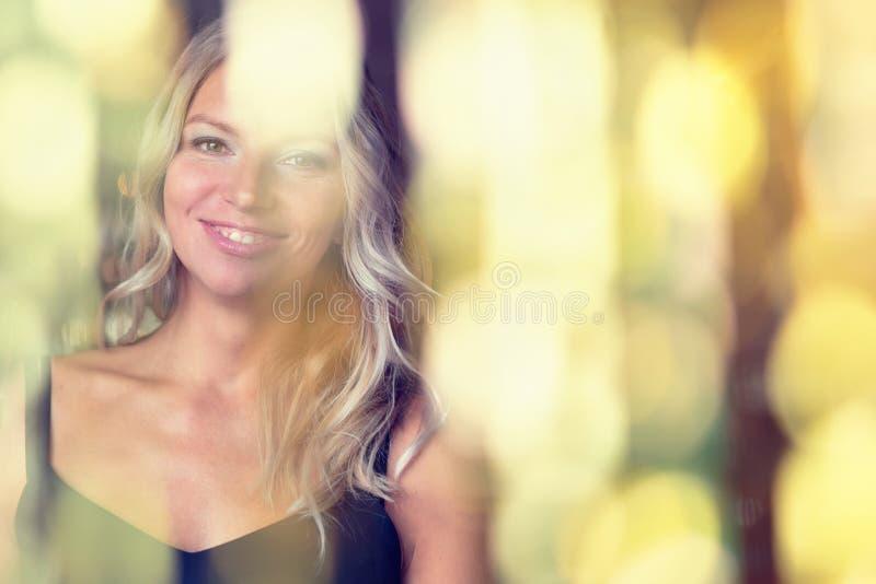 Szczęśliwa uśmiechnięta kobieta na złotym świątecznym światła tle zdjęcia stock