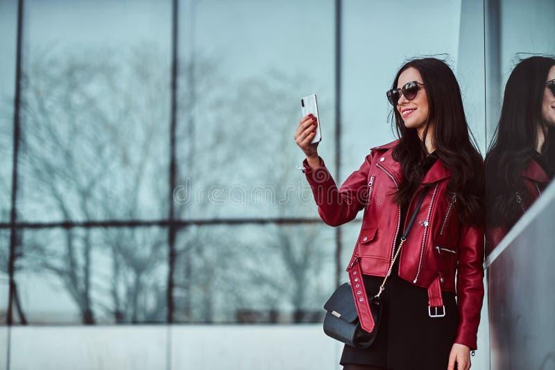 Szczęśliwa uśmiechnięta kobieta w czerwonej kurtce i okularach przeciwsłonecznych cieszy się chodzić outside podczas gdy brać sel zdjęcia stock