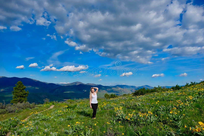 Szczęśliwa uśmiechnięta kobieta wycieczkuje w łąkach obraz royalty free