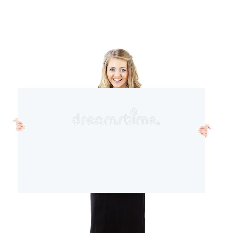 Szczęśliwa uśmiechnięta młoda biznesowa kobieta pokazuje pustego signboard zdjęcie royalty free